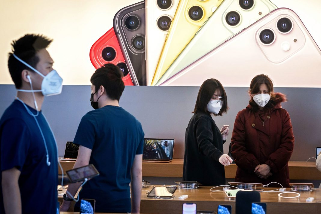 Apple staff and customers, wearing facemasks to protect against the COVID-19 coronavirus, are seen on the shop premises in Beijing on February 22, 2020.