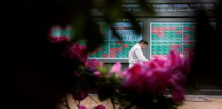 A passerby walks past in front of a stock quotation board outside a brokerage in Tokyo