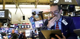 Traders work on the floor at the New York Stock Exchange (NYSE) in New York, U.S., February 27, 2020.
