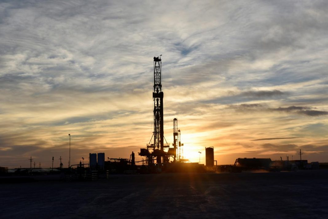 Drilling rigs operate at sunset in Midland, Texas, U.S.
