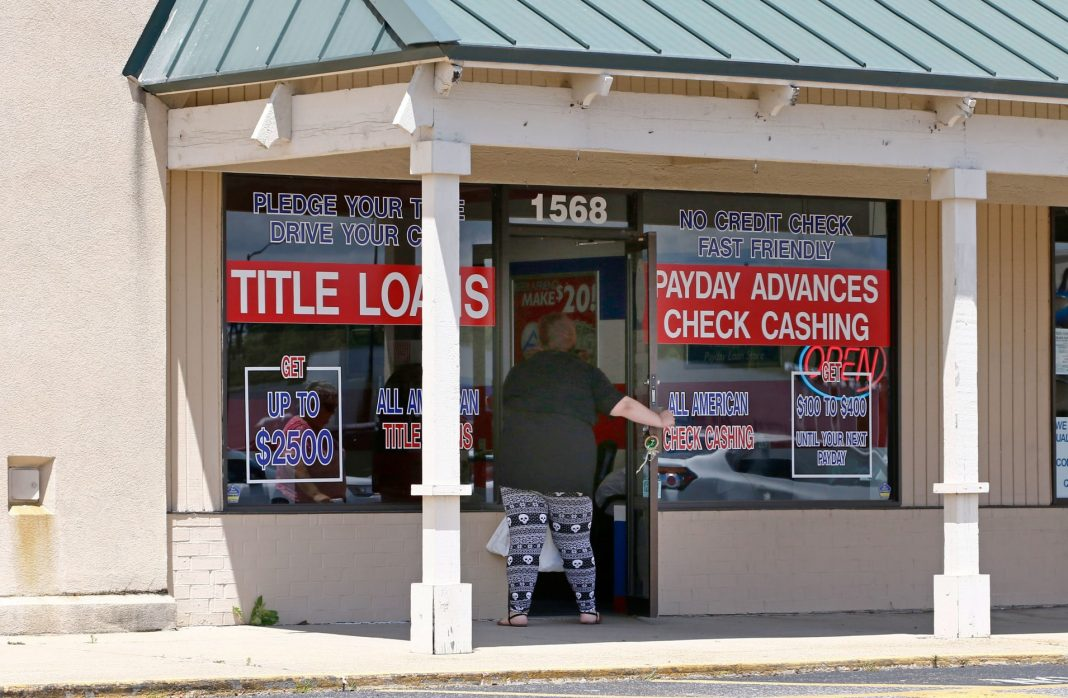 A woman enters an All American Check Cashing location in Brandon, Miss