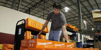 James Tahaney loads textbooks on to a pallet in preparation for shipping at the Chegg Inc. warehouse in Shepherdsville, Kentucky, U.S.