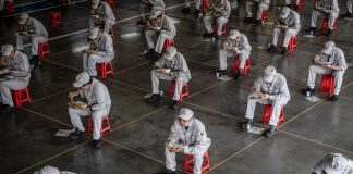 This photo taken on March 23, 2020 shows employees eating during lunch break at an auto plant of Dongfeng Honda in Wuhan in China's central Hubei province.