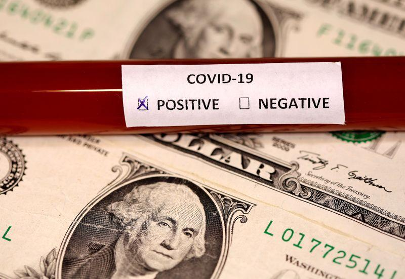 A test tube labelled with the coronavirus is placed on U.S. dollar banknotes