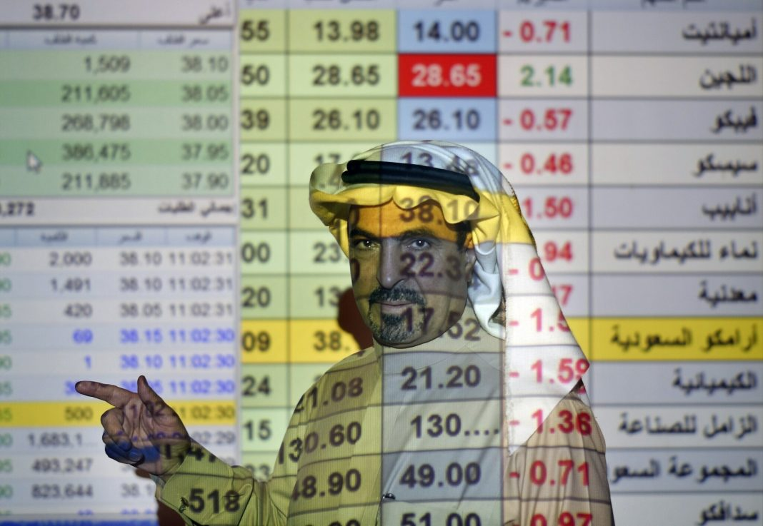 FILE- In this Thursday, Dec. 12, 2019, file photo, a trader talks to others in front of a screen displaying Saudi stock market values at the Arab National Bank in Riyadh, Saudi Arabia. Saudi Arabian oil company Aramco's initial public offering raised $29.4 billion, more than previously announced after the company said Sunday it used a so-called