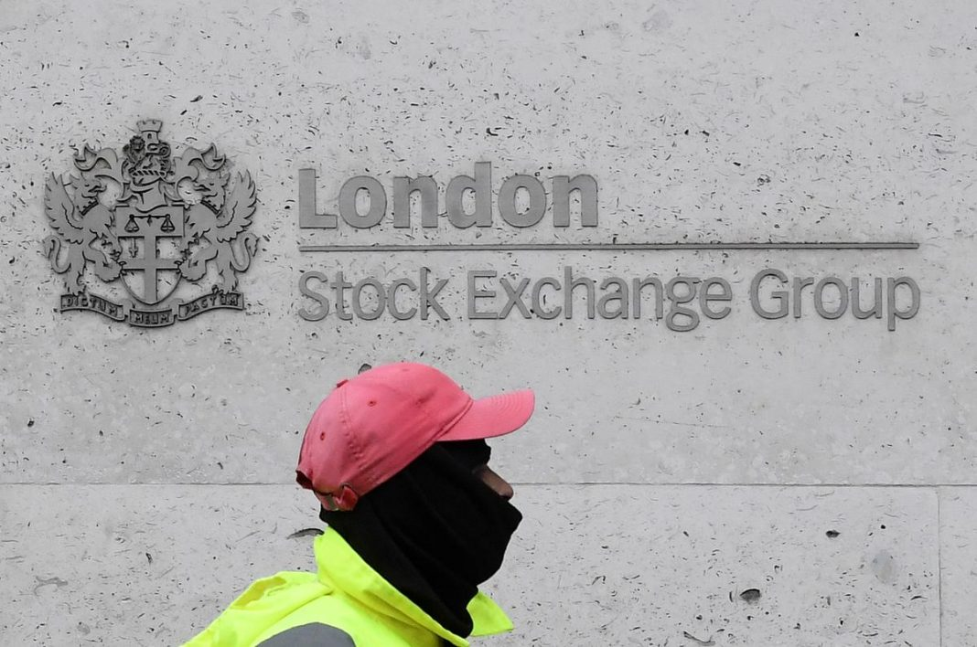 A street cleaning operative walks past the London Stock Exchange Group building in the City of London financial district, whilst British stocks tumble as investors fear that the coronavirus outbreak could stall the global economy, in London, Britain