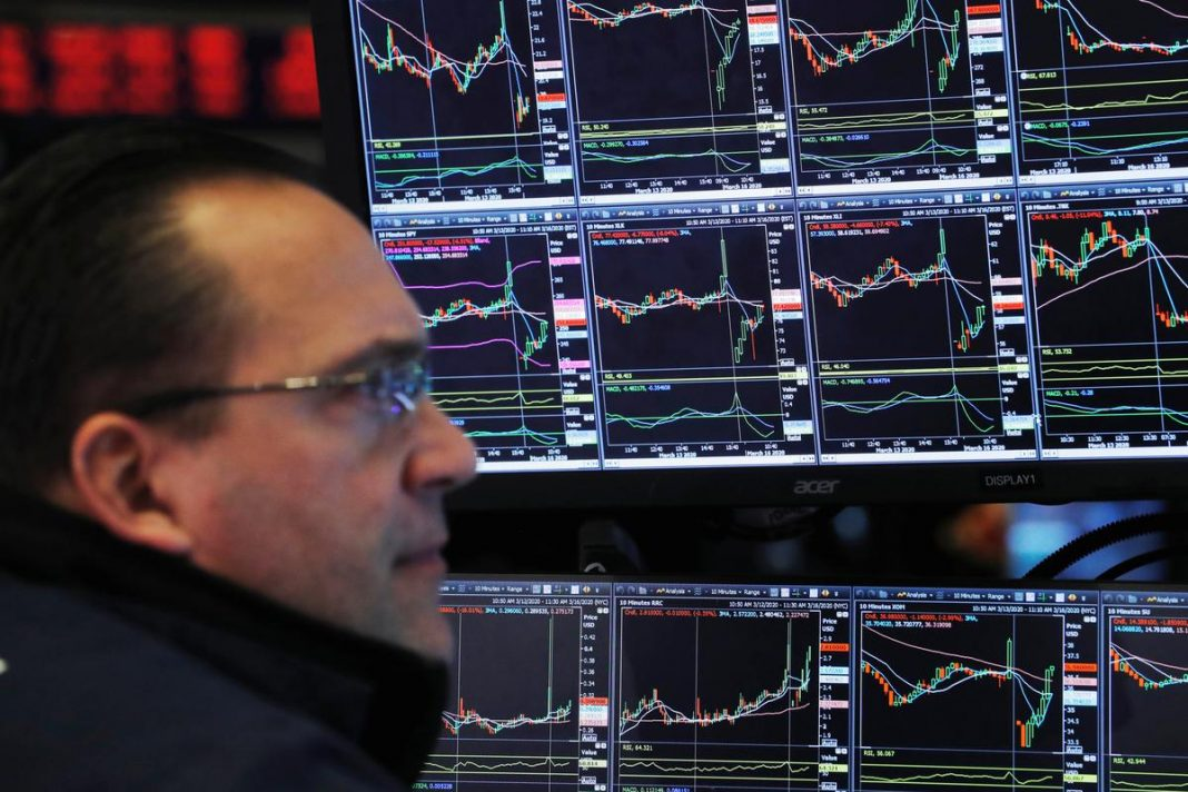 A trader works on the floor of the New York Stock Exchange shortly after the opening bell in New York, U.S.