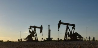 Pump jacks operate in front of a drilling rig in an oil field in Midland, Texas U.S.