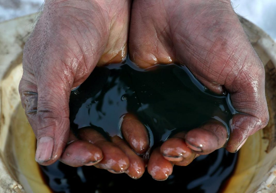 An employee holds a sample of crude oil at the Yarakta oilfield, owned by Irkutsk Oil Co, in the Irkutsk region