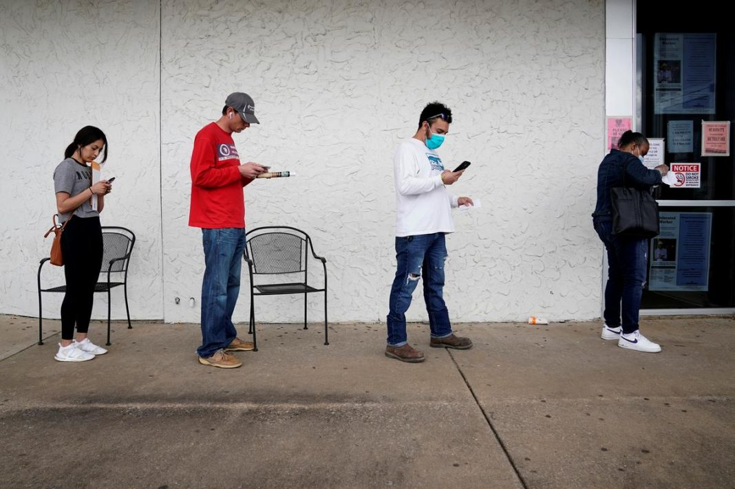 People who lost their jobs wait in line to file for unemployment following an outbreak of the coronavirus disease (COVID-19), at an Arkansas Workforce Center in Fayetteville, Arkansas, U.S.