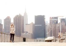 Pedestrians walk through a park, with the skyline of Manhattan rising behind them, amid the coronavirus disease (COVID-19) outbreak, in the Queens borough of New York City, U.S.