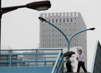 A man wearing a protective face mask, following the coronavirus disease (COVID-19) outbreak, walks on a pedestrian overpass at a business district in Tokyo, Japan