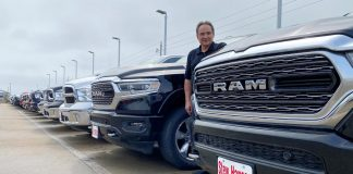 Jerry Bill, general manager of Stew Hansen Chrysler Dodge Jeep Ram, poses among a line of Ram trucks that he fears will be in very short supply by June if consumer demand remains strong, in Urbandale, Iowa, U.S.