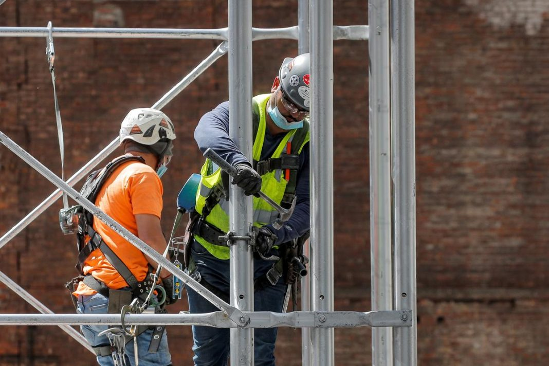 Construction workers assemble a scaffold at a job site, as phase one of reopening after lockdown begins, during the outbreak of the coronavirus disease (COVID-19) in New York City, New York, U.S.