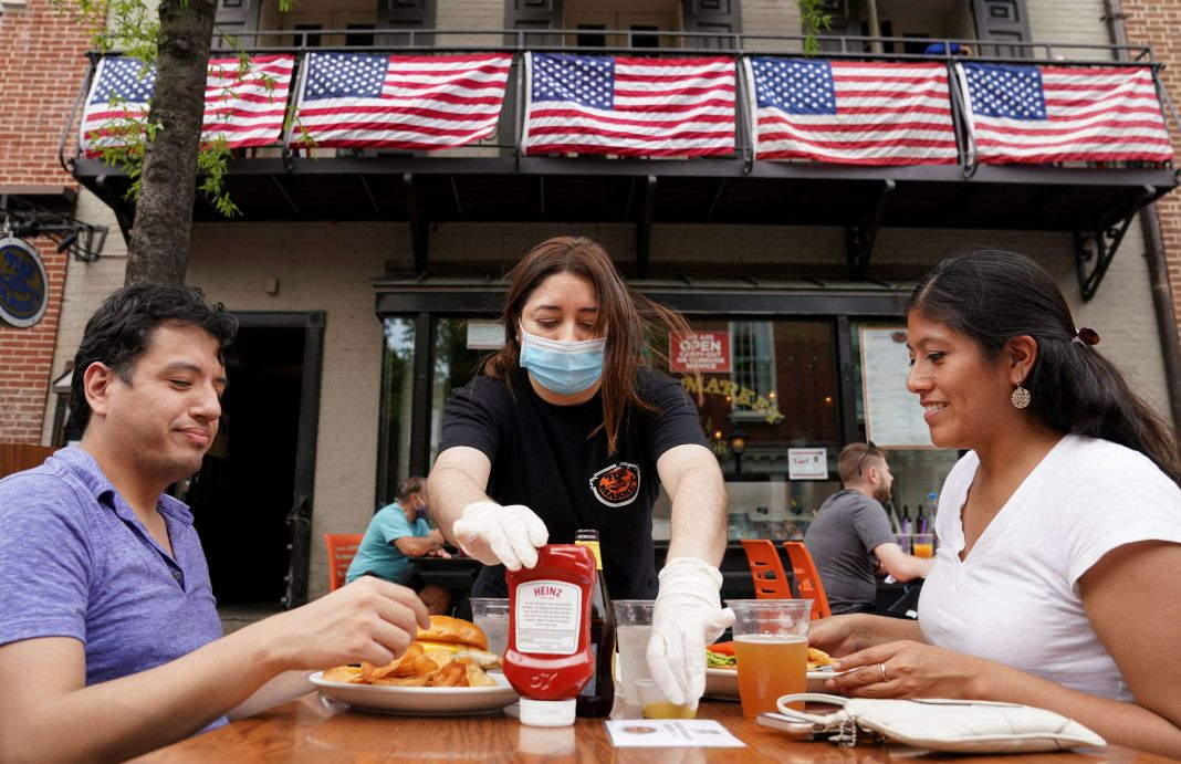 As Phase One of reopening begins in Northern Virginia, a waitress with a face mask to protect against the coronavirus disease (COVID-19) serves diners at a restaurant in Alexandria, Virginia, U.S.