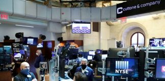 Traders wearing masks work, on the first day of in person trading since the closure during the outbreak of the coronavirus disease (COVID-19) on the floor at the New York Stock Exchange (NYSE) in New York, U.S.
