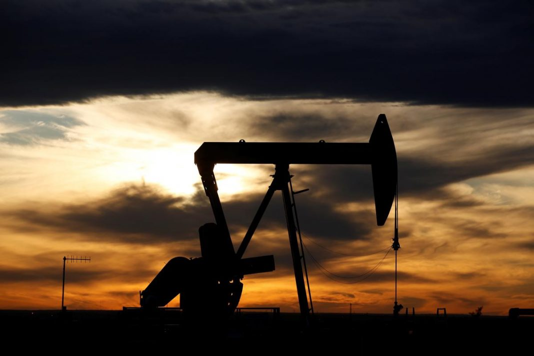 The sun sets behind a crude oil pump jack on a drill pad in the Permian Basin in Loving County, Texas, U.S.