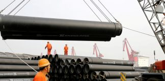 Workers direct a crane lifting ductile iron pipes for export at a port in Lianyungang, Jiangsu province, China June