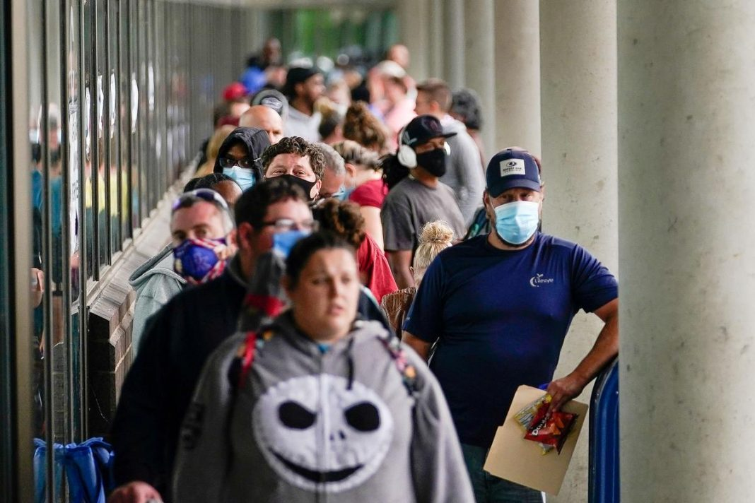 Hundreds of people line up outside a Kentucky Career Center hoping to find assistance with their unemployment claim in Frankfort, Kentucky, U.S. June