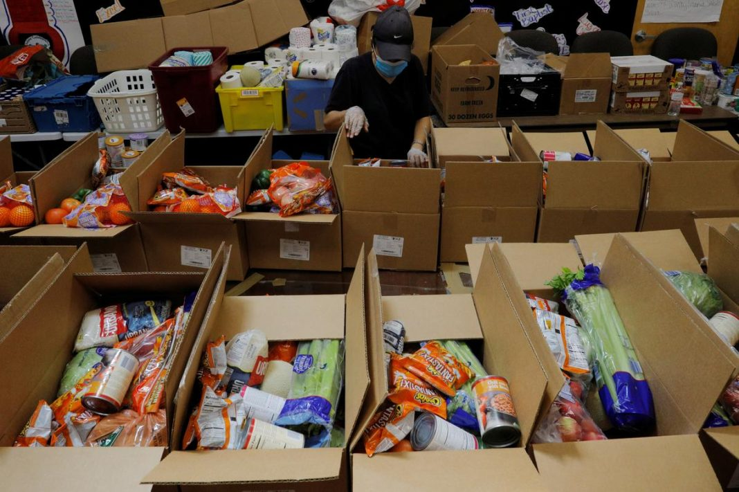 A worker prepares boxes of free food for distribution at the Chelsea Collaborative, which distributes 6 to 7 thousand of boxes of food a week in a city hard hit by the coronavirus disease (COVID-19) outbreak, in Chelsea, Massachusetts, U.S., July