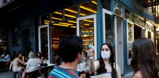 A waitress takes the temperature of customers as they arrive to eat at Dudley's as restaurants are permitted to offer al fresco dining as part of phase 2 reopening during the coronavirus disease (COVID-19) outbreak in the Lower East Side neighborhood of Manhattan in New York City, U.S.