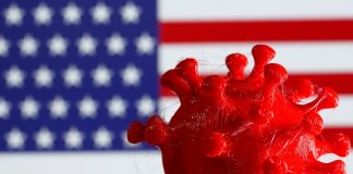 A 3D-printed coronavirus model is seen in front of a U.S. flag on display in this illustration taken March