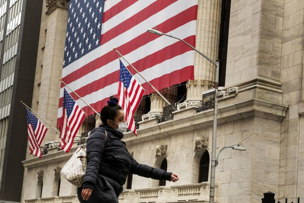 A pedestrian with a mask walks past of the New York Stock Exchange (NYSE) in New York, U.S., March